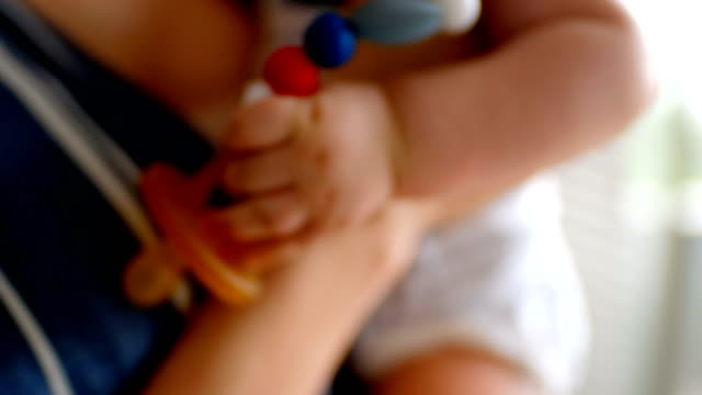 cute little baby carrying pacifier and mother holding him at home 4k - ciuccio video stock e b–roll