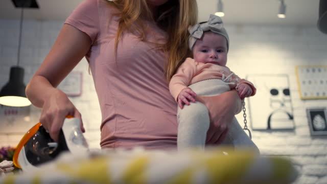 家事をしている母親に抱かれたかわいい赤ちゃん ビデオ