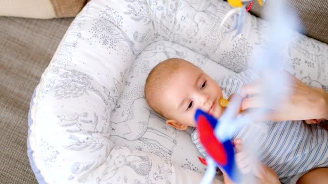 vídeos de stock, filmes e b-roll de bebezinho deitado no berço e mãe colocar a chupeta na boca 4k - bico