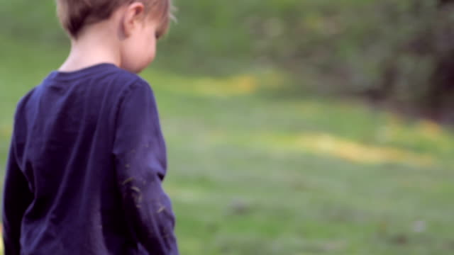 Cute little blond boy on grass turning to look at camera in slow motion. video
