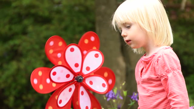 Cute Little Blond Girl Blows at Pinwheel in Nature video