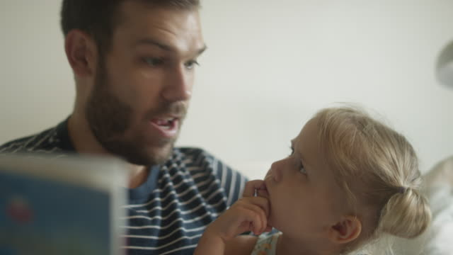 Cute little blonde girl listens curiously as father reads to her Cute little blonde girl listens curiously as father reads to her pigtails stock videos & royalty-free footage