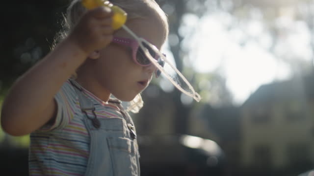 A cute little blonde girl wearing sunglasses blows bubbles on a sunny day A cute little blonde girl wearing sunglasses blows bubbles on a sunny day pigtails stock videos & royalty-free footage