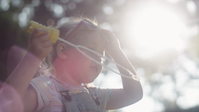 A cute little blonde girl wearing sunglasses blows bubbles with her daddy on a sunny day A cute little blonde girl wearing sunglasses blows bubbles with her daddy on a sunny day pigtails stock videos & royalty-free footage
