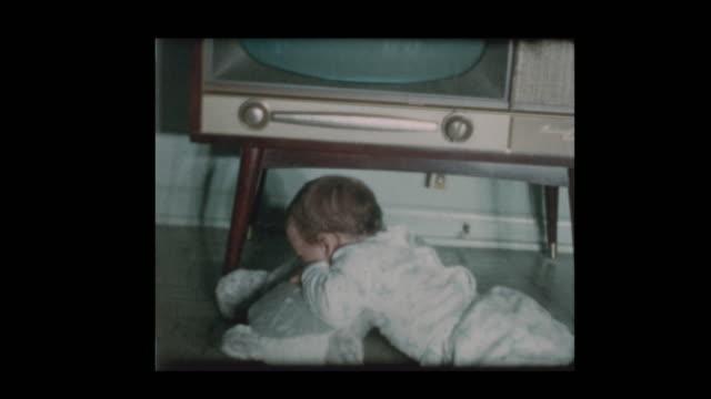 cute little boy checks out antique television set 1960 - устаревший стоковые видео и кадры b-roll