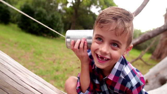 Cute little Boy curiously listening on tin can phone in park