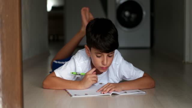 sevimli küçük çocuk ödevini yapıyor - çalışma kitabı stok videoları ve detay görüntü çekimi