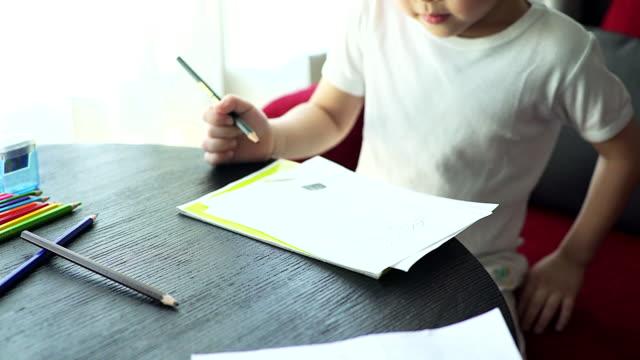 4 K: かわいい男の子の宿題、ぬり絵、書くと絵画します。子供を描きます。子供を描画します。家で本を持つ幼児。幼児を読み書きすることを学ぶ。 ビデオ