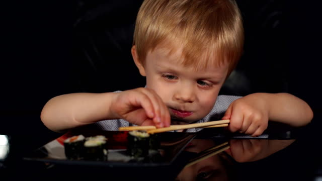 Cute little boy eat sushi with wooden chopsticks. video