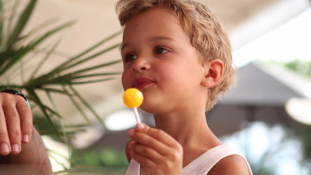 Cute little boy eats a lollipop. Child eating lollipop