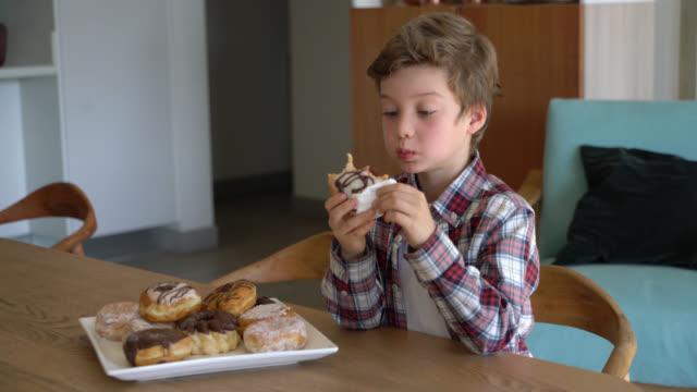 bambino carino che si gode una deliziosa ciambella a casa - 8 9 anni video stock e b–roll