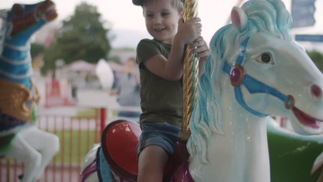 Cute little boy  enjoying merry-go-round ride at amusement park Happy child riding carousel horse at amusement park in summer. Shot using BMPCC 4k. outdoor play equipment stock videos & royalty-free footage