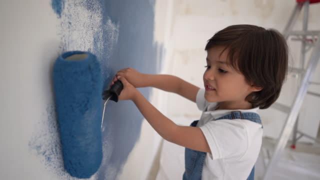 vidéos et rushes de petit garçon mignon appréciant la peinture avec un rouleau de peinture au sourire à la maison - hlm