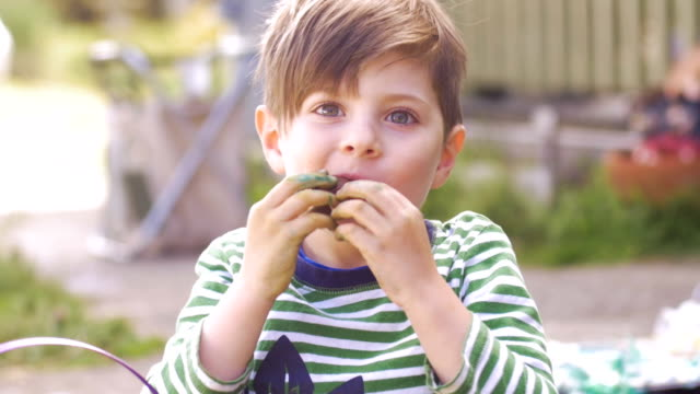 Cute little boy giving thumbs up while enjoying eating chocolate in slow motion video