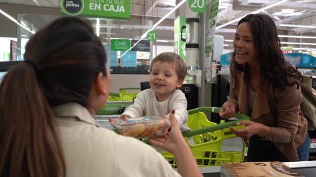 симпатичный маленький мальчик вручая продукты кассиру, стоя в корзине и мама рядом с ним все улыбаются в супермаркете - касса стоковые видео и кадры b-roll