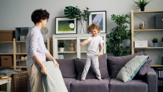 söt liten pojke ha kul med kudde slåss med sin mamma på soffan hemma - cosy pillows mother child bildbanksvideor och videomaterial från bakom kulisserna