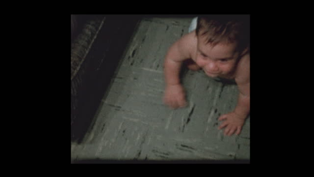 cute little boy in diapers crawls around and plays to camera - hotel reception filmów i materiałów b-roll