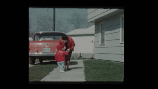 1961 Cute little boy in red coat and hat with mother and antique car