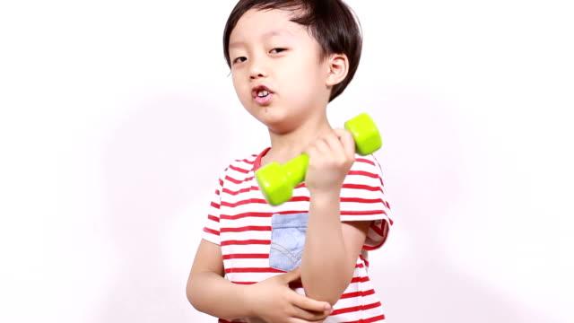 Cute little boy lifting weights