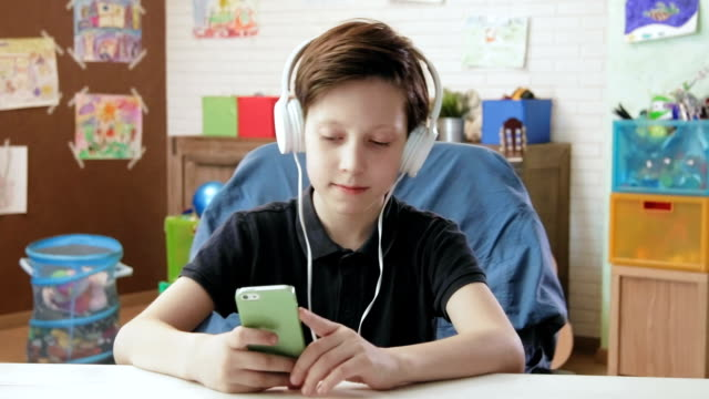 cute little boy listening to music on his smartphone wearing headphones - solo bambini maschi video stock e b–roll
