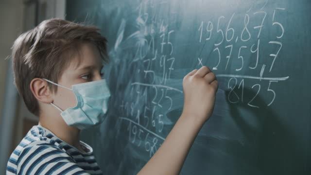 stockvideo's en b-roll-footage met leuk weinig jongen op mathles tijdens covid-19 pandemie - schooljongen