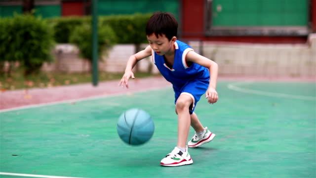 söt liten pojke spela basket - basketboll boll bildbanksvideor och videomaterial från bakom kulisserna