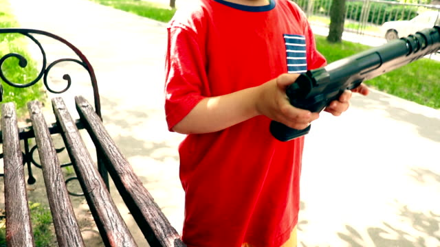 Cute little boy playing with a big toy gun in the park outdoors - stock video