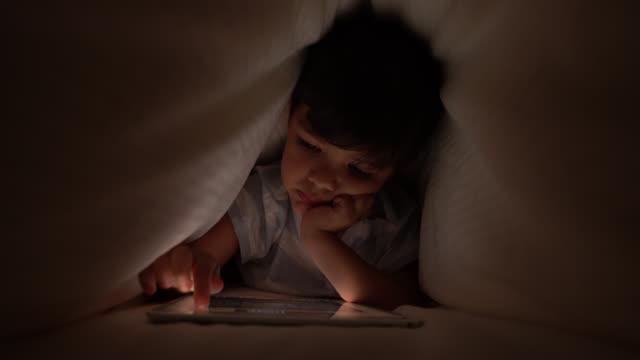 sevimli küçük çocuk mide üzerinde yatan çarşaf altında onun dijital tablet ile oynuyor - dijital yerli stok videoları ve detay görüntü çekimi