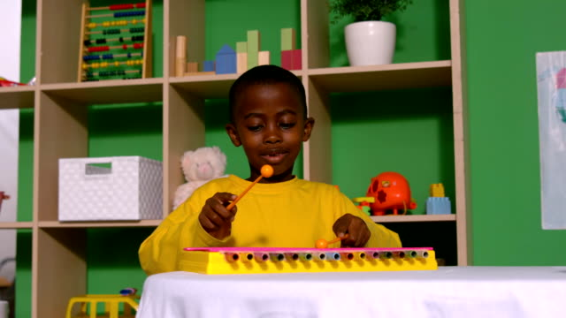 stockvideo's en b-roll-footage met cute little boy playing xylophone in classroom - lagere schoolleeftijd