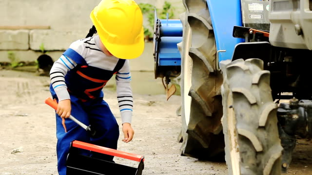 cute little boy repairing a tractor wheel - agricultural machinery stock videos & royalty-free footage