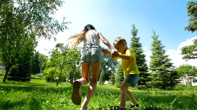 cute little boy runs away from his happy sister through the spruce trees at sunny day - brother stock videos and b-roll footage