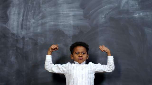 cute little boy showing biceps - napinać mięśnie filmów i materiałów b-roll