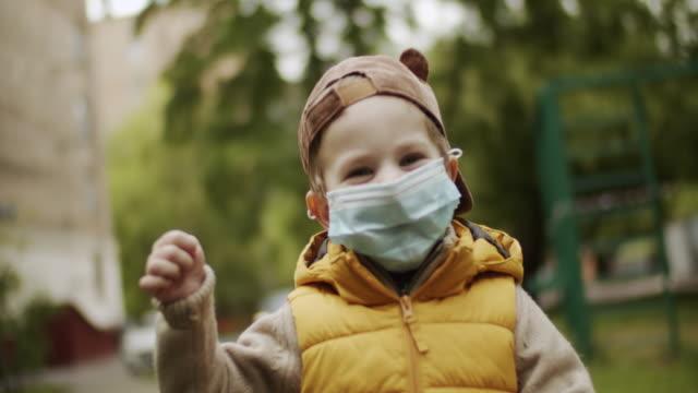vidéos et rushes de petit garçon mignon souriant derrière le masque protecteur à l'extérieur - enfant masque