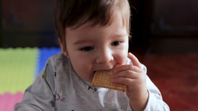 vídeos y material grabado en eventos de stock de lindo niño de pie en la sala de estar y comer galleta. niño sin dientes tratando de comer galleta en la sala de estar temprano en la mañana. el desayuno dulce es el mejor desayuno - galleta dulces