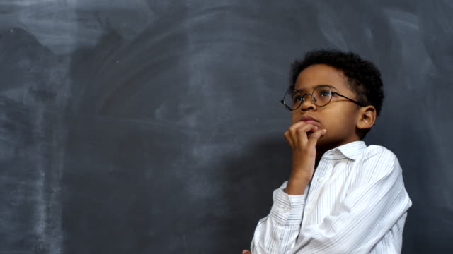 Cute Little Boy Thinking Portrait shot of pensive little African-American boy in glasses standing against blackboard and thinking about something with hand on chin thinking stock videos & royalty-free footage