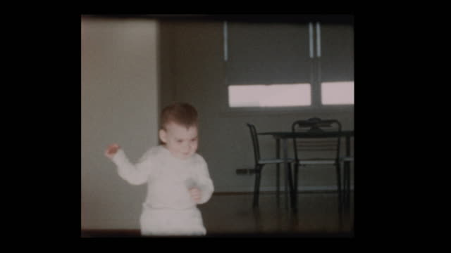 cute little boy toddler wanders around living room 1960 - hotel reception filmów i materiałów b-roll