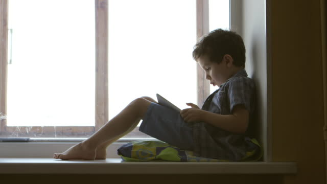 side view: a cute little boy uses a white tablet pc on a windowsill at home - middle shot - tylko dzieci filmów i materiałów b-roll