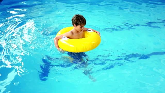 cute little boy using inflatable ring in the pool - inflatable ring bildbanksvideor och videomaterial från bakom kulisserna