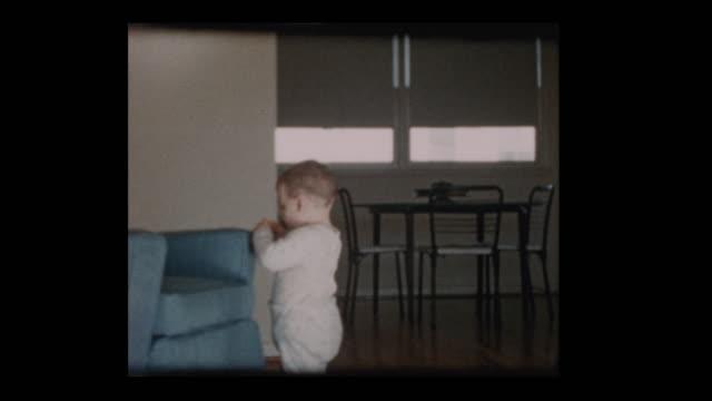 1960 cute little boy wandering around living room - hotel reception filmów i materiałów b-roll