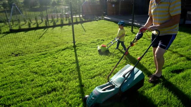 Cute little boy with gardener man mowing cutting grass lawn. Gimbal movement