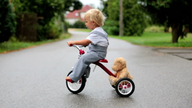 Cute little boy, with teddy bear toy, riding tricycle on the street in the rain, barefeet, summertime
