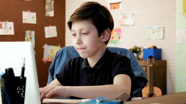 Niedliche kleine Junge Aufsatz für die Schule in seinem Zimmer Hausaufgaben – Video