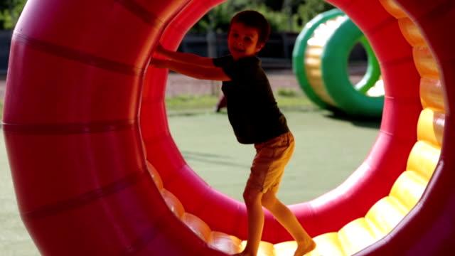 söta små pojkar, spelar i en rullande plast cylinder ring med ett hål i mitten, utomhus - inflatable ring bildbanksvideor och videomaterial från bakom kulisserna