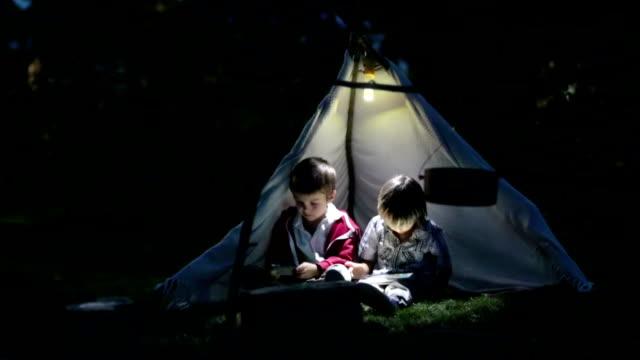 söta små bröder, spelar på surfplatta och telefon på natten i campside, i tältet - digital reading child bildbanksvideor och videomaterial från bakom kulisserna