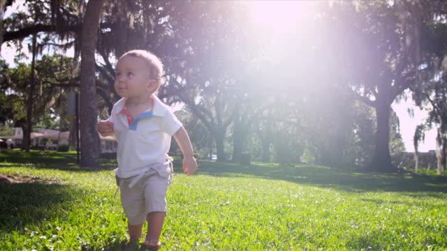 Cute Little Caucasian Boy First Steps Outdoors Park video