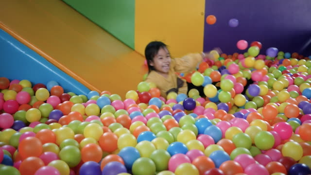 cute little child girl having fun to playing slide in plastic dry pool with colorful balls inside the kids playground indoor. - stanza dei giochi video stock e b–roll