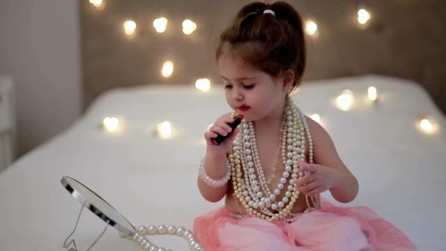 Cute little child putting on lipstick