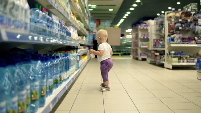 Cute little child walking in water department in the supermarket and choosing bottles inside of a big marketplace, carefully thinking about products to buy Cute little child walking in water department in the supermarket and choosing bottles inside of a big marketplace, carefully thinking about products to buy. girl power stock videos & royalty-free footage