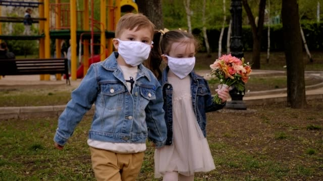 Cute little childs in medical masks hold hands in the Park,a girl with a flowers