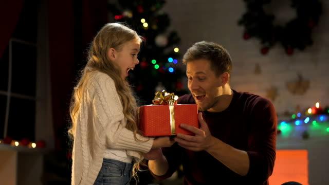 söt liten dotter ger julklapp till glad pappa, lyser mousserande - christmas gift family bildbanksvideor och videomaterial från bakom kulisserna